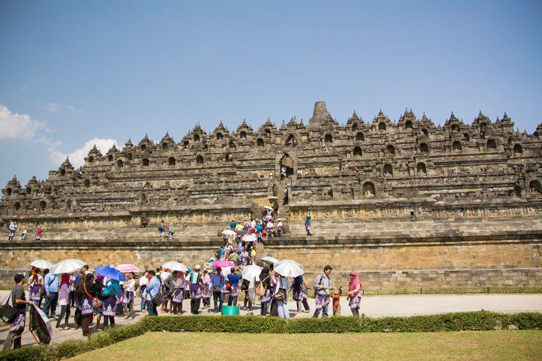 La foule de touristes avec des ombrelles au pied du temple de Borobudur en Indonésie