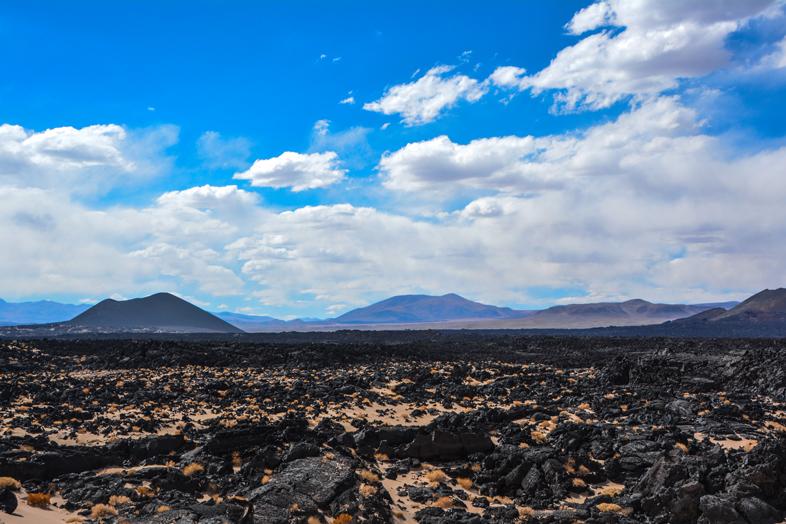 Champ de lave et vue sur les volcans en arrière-plan