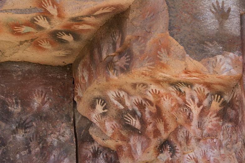 Peintures rupestres sur une paroi pleine de traces de mains peintes dans la Cueva De Las Manos en Argentine