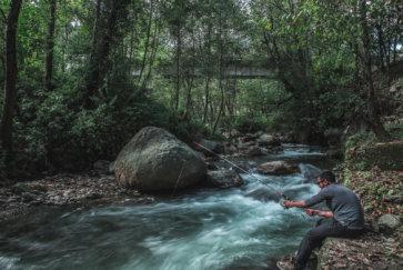 Un homme pêche dans la rivière d'une forêt en France